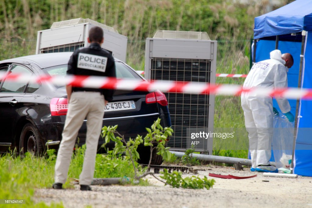 Police investigators and forensic experts work on April 25, 2013 at the site where the president of the Corsica Regional National Parc (PNRC), Jean-Luc Chiappini, 65, was shot dead returning from the Napoléon-Bonaparte airport in Campo dell'Oro, outside the southwestern city of Ajaccio on the French Mediterranean island of Corsica. It is the 10th homicide perpetrated in Corsica, an island of 310,000 inhabitants, in 2013.
