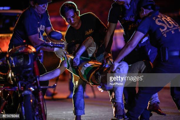 Police investigators carry the body of a man after he was killed by unknown assailants in Quezon city Metro Manila Philippines July 18 2017 The...