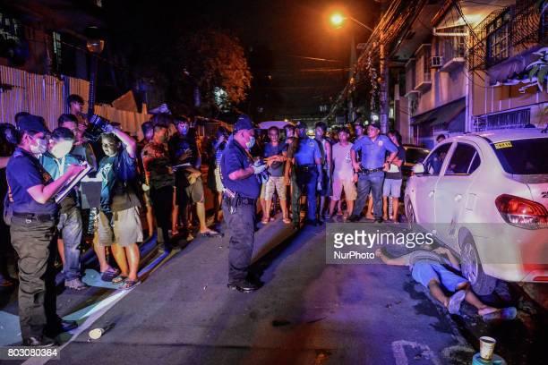 Police investigators examine the body of a shooting victim in Manila Philippines June 11 2017 Drugrelated killings continue as President Rodrigo...