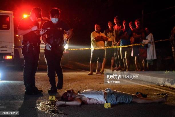 Police investigators examine the body of Irish Glorioso who was shot dead by unknown assailants in Navotas north of Manila Philippines June 8 2017...