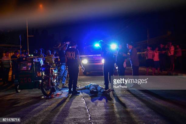 Police investigators inspect the body of a man after he was killed by unknown assailants in Quezon city Metro Manila Philippines July 18 2017 The...