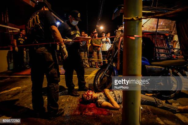 Police investigators inspect the body of a man who was killed by an unknown assailant in Mandaluyong Metro Manila Philippines August 19 2017 Amidst...