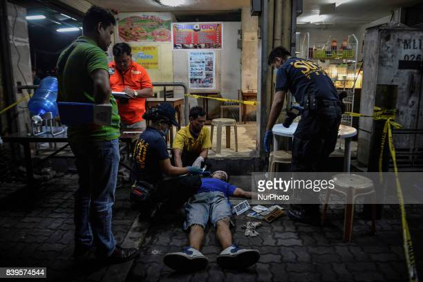 Police investigators inspect the body of a man who was killed by unknown assailants in Manila Philippines August 17 2017 Amidst the drug crackdown's...