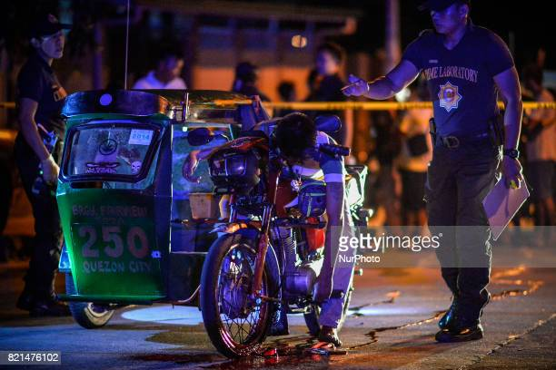 Police investigators inspect the body of man lying dead on a tricycle after he was killed by unknown assailants in Quezon city Metro Manila...