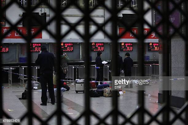 Police investigators inspect the scene inside the Kunming railway station after an attack in Kunming southwest China's Yunnan province on March 2...