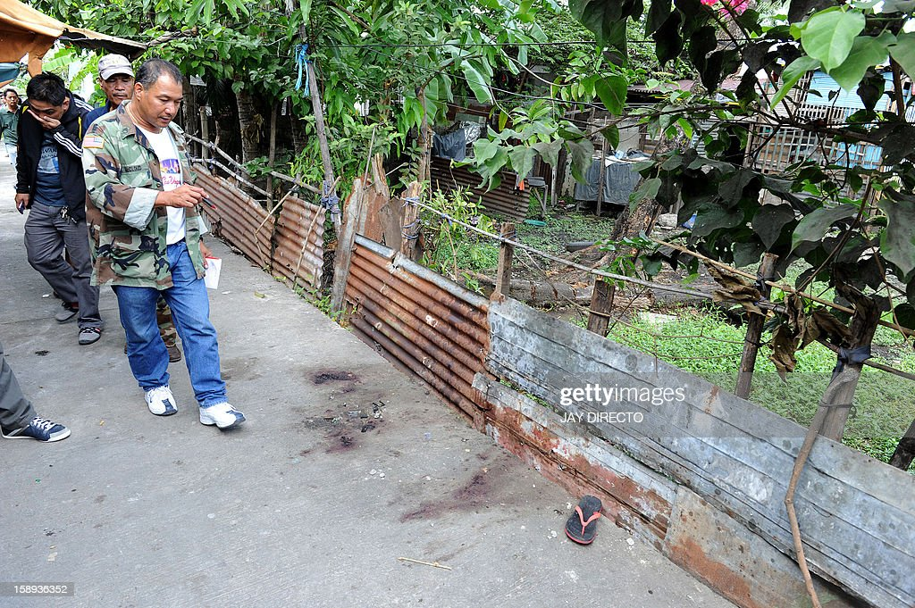 Police investigators inspect where a gunman was shot dead during a gunbattle with police in Kawit, about 40 kms (25 miles) south of Manila on January 4, 2013. The gunman armed with a semi-automatic pistol killed at least five people and wounded 11 others as he rampaged through a slum on the outskirts of the Philippine capital, authorities said.