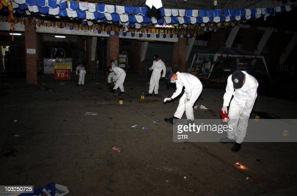 Police investigators look for evidence at the site of bomb explosion outside the airport terminal building in Zamboanga City on the southern...
