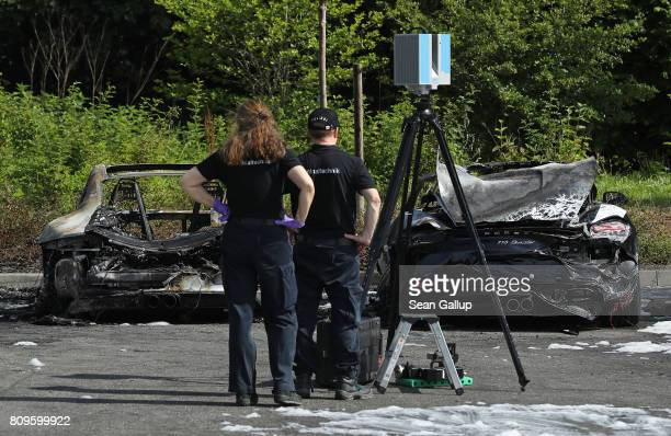 Police investigators stand before two Porsche cars that were among 10 set alight by an arsonist at a Porsche dealership on July 6 2017 in Hamburg...