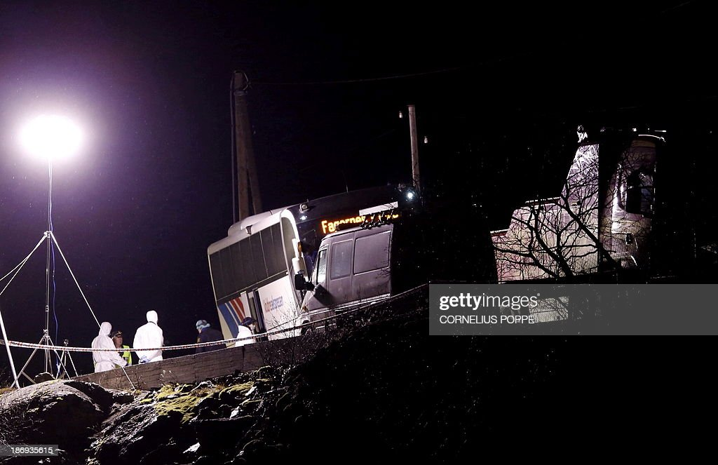 Police investigators stand in front of a hijacked bus in Ardal, western Norway, early on November 5, 2013. Three people were killed when a man armed with a knife hijacked a bus in western Norway on November 4, 2013, according to police, who have arrested a suspect they say comes from South Sudan. The long-distance bus was on the route between the mountainous Valdres region, a popular area for skiing, and the Norwegian capital Oslo. AFP PHOTO / NTB SCANPIX / CORNELIUS POPPE
