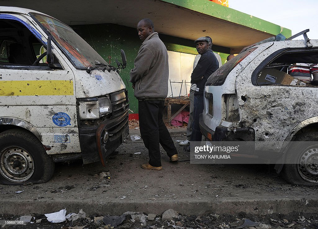 Police investigators stand next to vehicles bearing signs of shrapnel damage at the scene of a suspected bomb attack in Nairobi's Eastleigh suburb, on November 18, 2012. Seven people were killed and many more wounded when an apparent explosive device was hurled at a packed minibus in a predominantly Somali area of the Kenyan capital Nairobi today, police and the Red Cross said. Nairobi police chief Moses Nyakwama said the blast occurred on a so-called 'matatu', or local minibus, in the district of Eastleigh, where mainly Somalis or Kenyans of Somali origin live and which has been the target of other attacks in recent weeks. AFP PHOTO/Tony KARUMBA