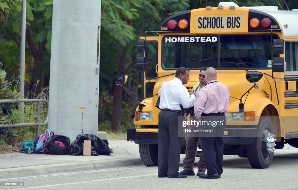 Police investigators stand outside a school bus after a student shot and killed a 13-year-old girl in front of her younger sister and seven other children on a school bus Tuesday morning, November 20, 2012, in Homestead, Florida.