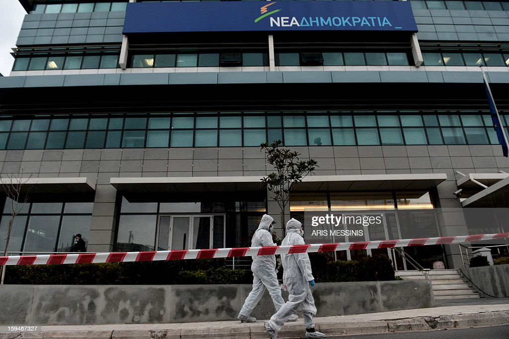 Police investigators walk on january 14, 2013 outside the headquarters of New Democracy conservative party in Athens. Shots were fired early on January 14 near the offices of main Greek ruling party New Democracy in Athens, police said, after a recent wave of arson attacks against political offices.