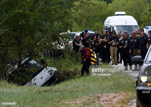 Police investigators watch as the van containing six members of the the Saldivar family who died is towed to the road after they crashed their van...