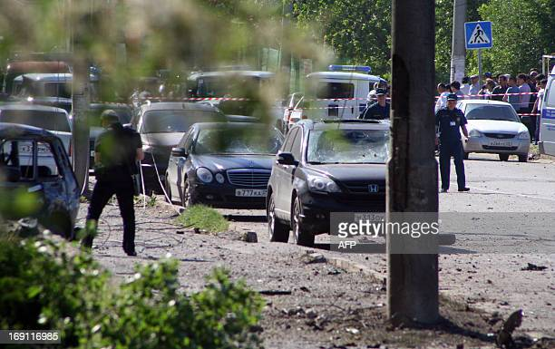 Police investigators work at a blast site outside a building used by court bailiffs in central Makhachkala on May 20 2013 At least three people were...