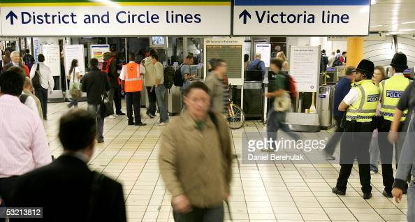 Police keep a watch as comuters make their way through the tube system during rush hour July 8 2005 in London At least 50 people were killed and 700...