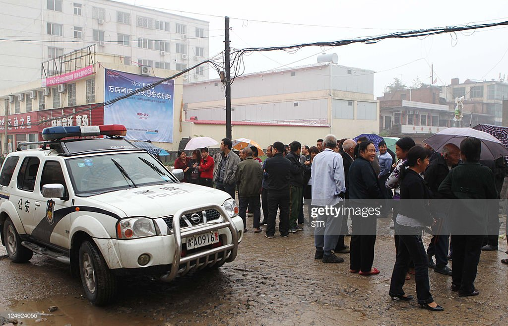 Police keep watch as family members of victims gather after a 30yearold attacker killed six people with an axe in Henan province's Gongyi city in...