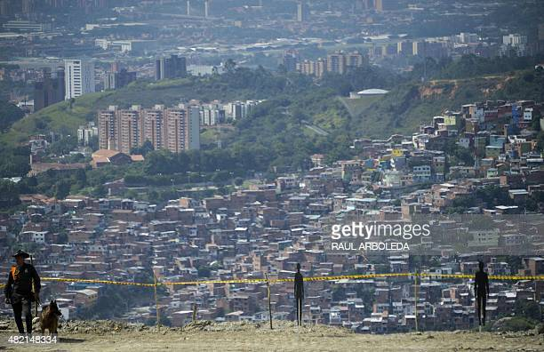 Police keep watch during a ceremony at 'La Escombrera' rubbish dump in the 13 Commune shantytown in Medellin Antioquia department Colombia on July 27...