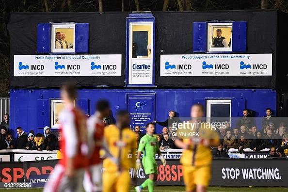 Police keep watch over the spectators during the English FA Cup fifth round football match between Sutton United and Arsenal at the Borough Sports...