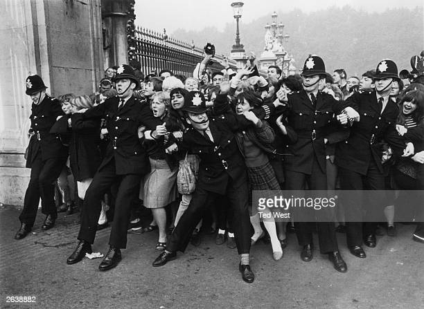 Police keeping back a crowd of young fans outside Buckingham Palace London as pop group the Beatles receive their MBEs