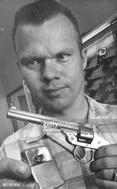 Police Lab Technician Charles Hoaglin He holds 22caliber revolver allegedly fired by Mike D Dominguez and policeman's lighter that stopped bullet...