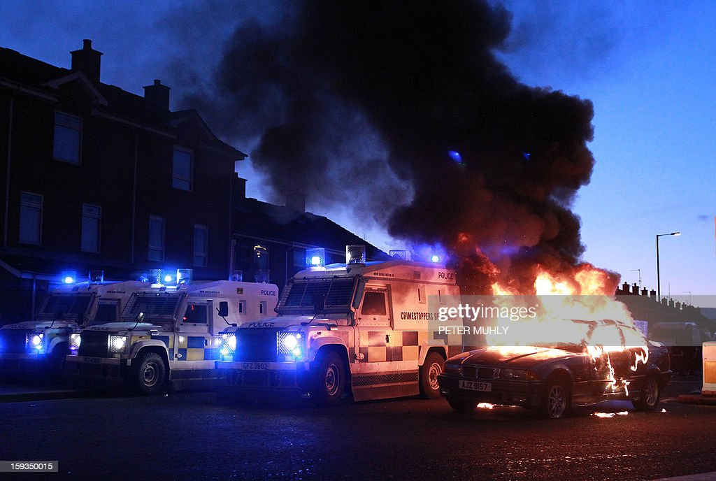 Police landrovers take up positions around a burning car during violence between, loyalists, nationalists and the police in east Belfast, Northern Ireland on January 12, 2013 after the latest loyalist march against the decision to limit the days on which the Union Flag would be flown over Belfast City Hall. Northern Irish demonstrators loyal to Britain clashed with nationalists and police on Saturday in fresh protests against curbs on flying the British flag, leaving four officers injured, police said. The clashes were the latest to blight the British province after more than five weeks of violent disorder over the flag issue.