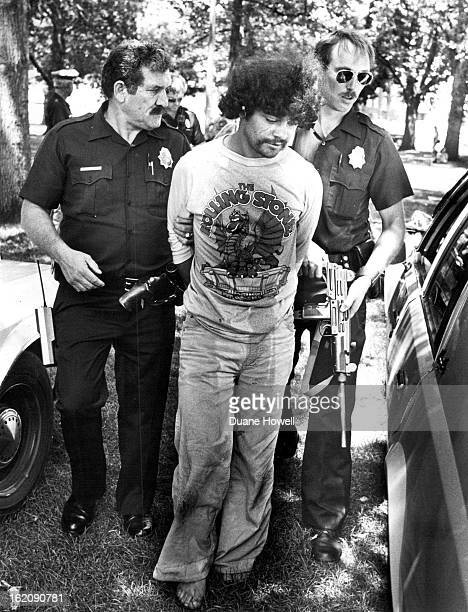 JUN 24 1982 Police lead away a suspect for having a concealed weapon Office at right holds the Uzi submachine gun Suspect identified by police as...
