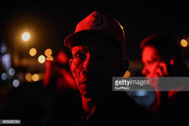 Police lights illuminate the face of Samuel Marino has he looks on at the scene where his daughter Cristita Padual was shot dead by unknown...