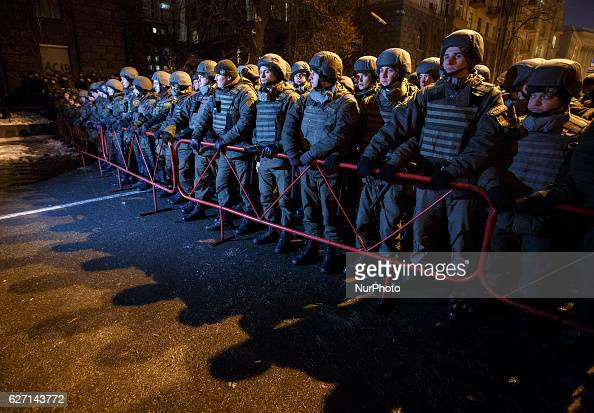 A police line stand in front of the Presidential office as smoke of smoke grenade hangs behind during a rally of activists and supporters of...