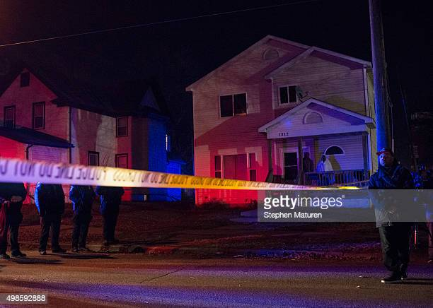 Police line up in front of a crime scene and two people look on from their porch after 5 people were shot at a Black Lives Matters protest November...