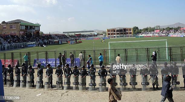 Police line up to control the crowds in Afghanistan Football Federation Stadium for the Afghanistan national team's first home soccer match since...