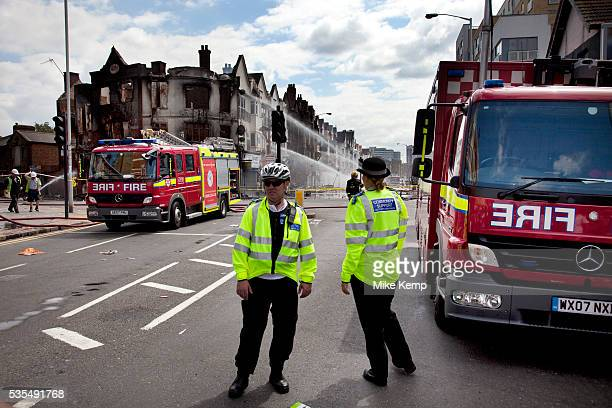 Police lines protect burnt out remains of a row of shops and flats on London Road in Croydon The day after rioting took place in Croydon in South...