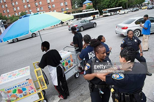 Police linger near icecream salesman near the area where riots broke out after the funeral for Freddie Gray last year June 23 2016 in Baltimore...