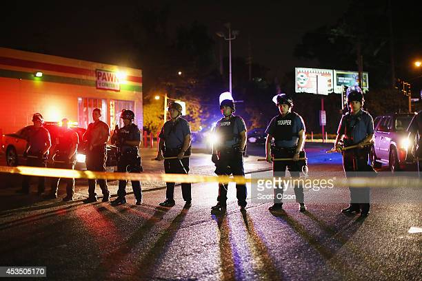 Police lock down a neighborhood on August 11 2014 in Ferguson Missouri Police responded with tear gas as residents and their supporters protested the...