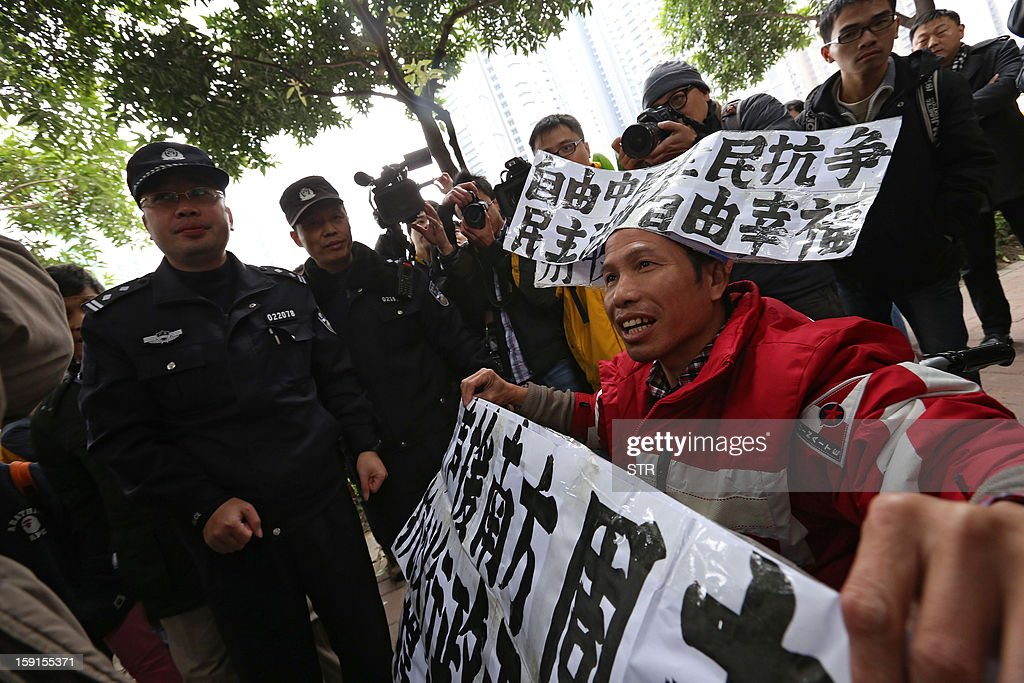 Police (L) look on as a man (R) protests as a group of people calls for greater media freedom outside the headquarters of Nanfang Media Group in Guangzhou on January 9, 2013. A Chinese weekly newspaper at the centre of rare public protests about government censorship will publish as usual on January 10, a senior reporter said, following reports of a deal to end the row. The row at the popular liberal paper, which had an article urging greater rights protection replaced with one praising the ruling communist party, has seen demonstrators mass outside its headquarters in the southern city of Guangzhou. AFP PHOTO