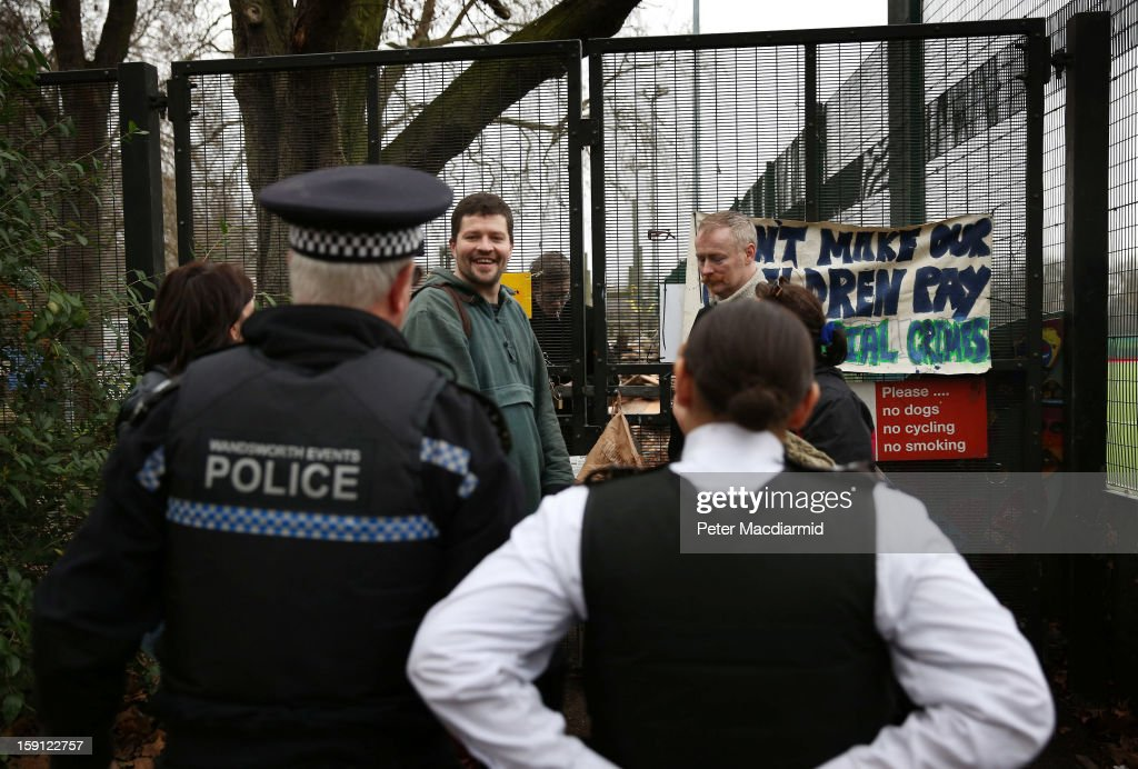 Police look on as activists speak at a gate to Battersea Park adventure playground on January 8, 2013 in London, England. Activists and local residents oppose local authority plans to demolish the adventure playground, which has been mostly used by teenagers, and replace it with facilities for younger children who will need less supervision.