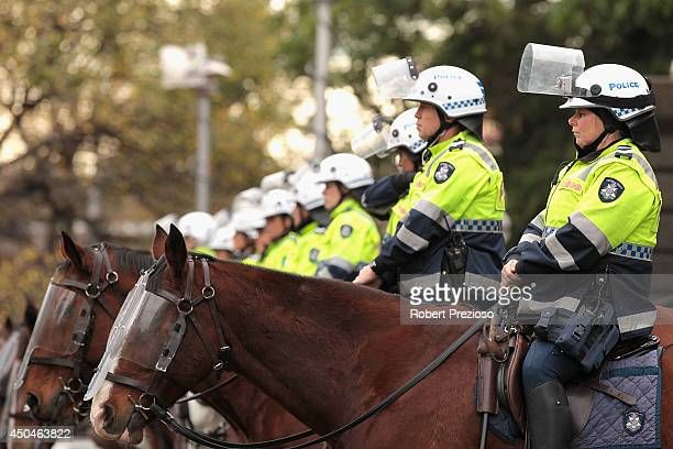 Police look on as protesters gather outside Parliament House during antigovernment rallies in Melbourne on June 12 2014 in Melbourne Australia...