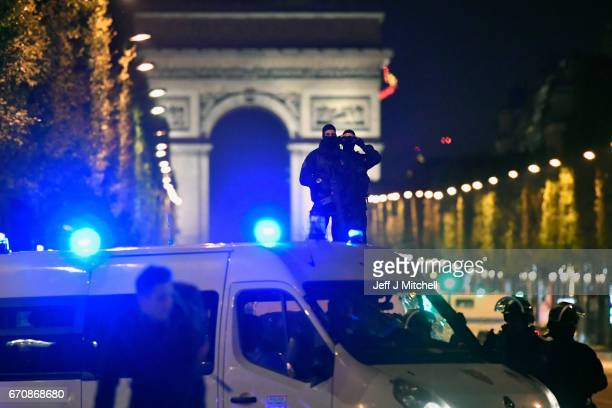Police Look through binoculars as officers secure the area after a gunman opened fire on Champs Elysees on April 20 2017 in Paris France One police...