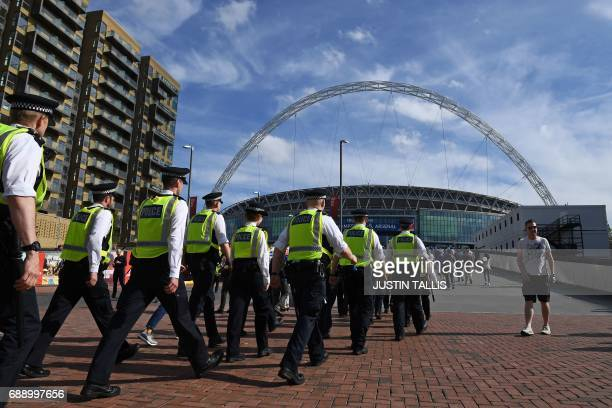 Police make their way to the Stadium in London on May 27 2017 ahead of the English FA Cup final football match between Arsenal and Chelsea at Wembley...
