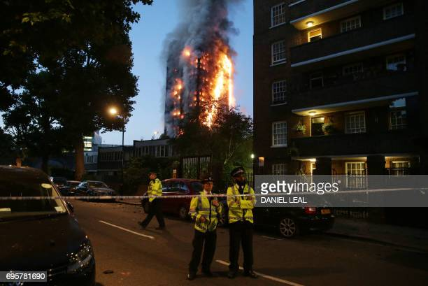 TOPSHOT Police man a security cordon as a huge fire engulfs the Grenfell Tower early June 14 2017 in west London The massive fire ripped through the...