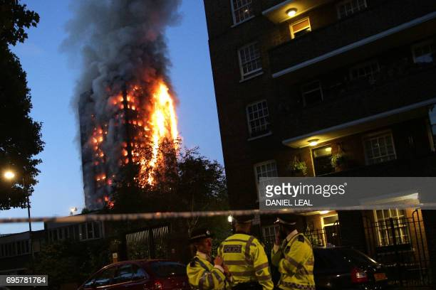 Police man a security cordon as a huge fire engulfs the Grenfell Tower early June 14 2017 in west London The massive fire ripped through the 27storey...