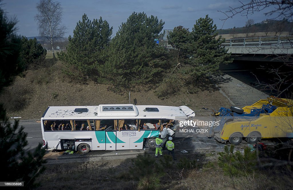 A police man and a technician inspect the site of a bus accident, carrying passengers from France, near Rokycany, Czech Republic, on April 08, 2013. 41 passengers were injured, a young woman died in the accident of a French bus on its way to Prague. AFP PHOTO / MICHAL CIZEK