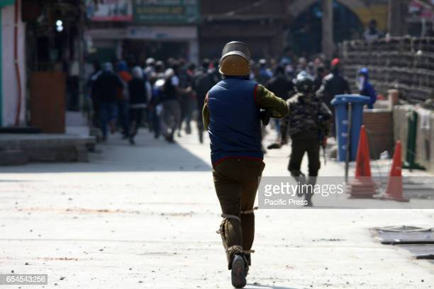 A police man chasing the stonepelters to fire tear gas canister to disperse them in old city Srinagar on Friday Indian Controlled Kashmir