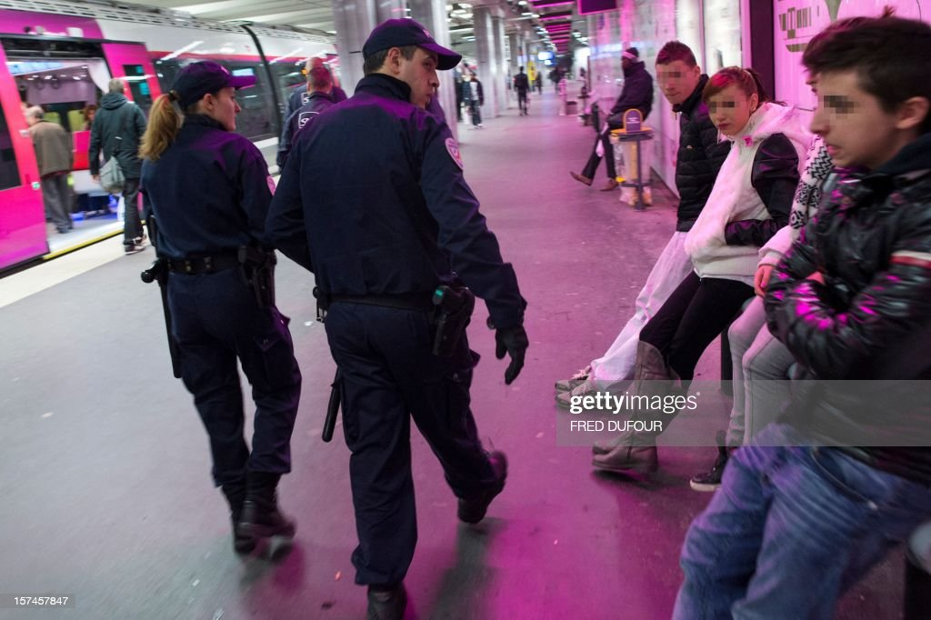 A police man looks back at youths sitting on a platform as they patrol the Gare du Nord (North railway station) in Paris on November 30, 2012 .
