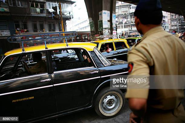 A police man looks on as Muslim Indian women ride a taxi past a condolence meeting following the series of terrorist attacks on the city on December...