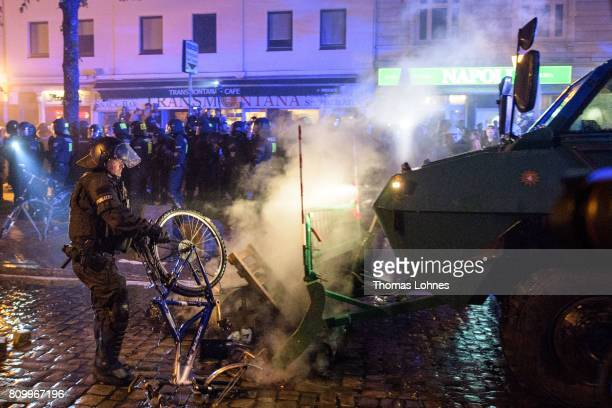 A police man removes a barricade from demonstrators after the 'Welcome to Hell' antiG20 protest march near the Rote Flora leftwing centre on July 6...