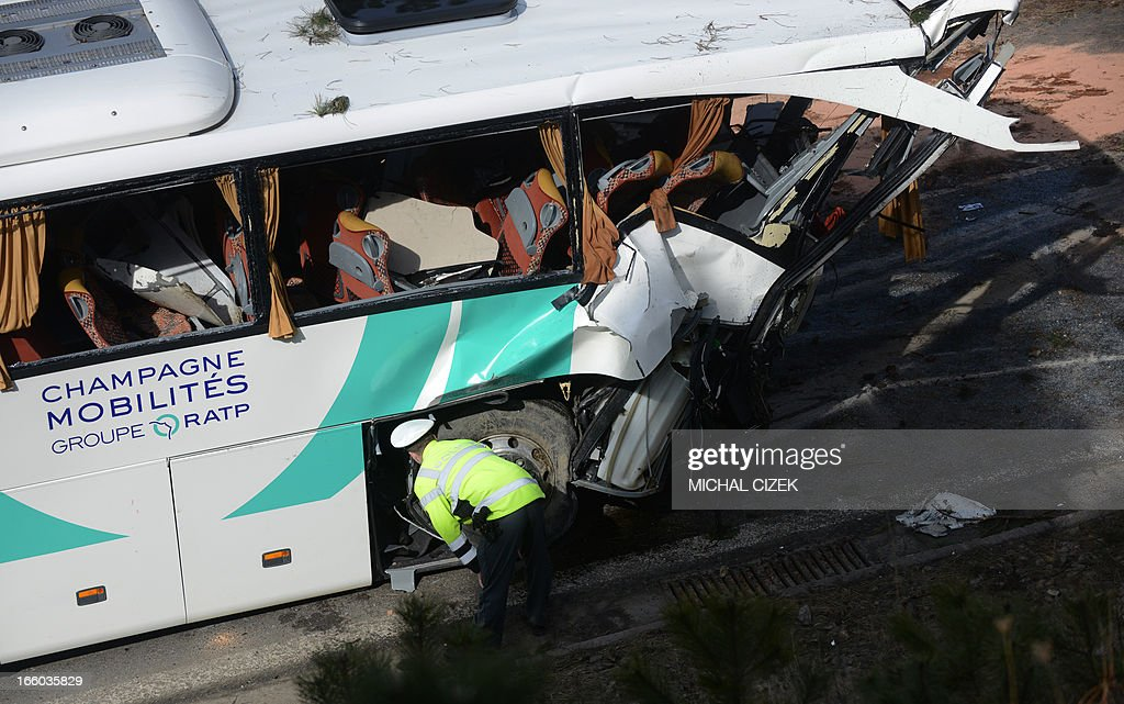 A police man searches an accidented French bus on its crash site near Rokycany, Czech Republic, on April 08, 2013. 41 passengers were injured, a young woman died in the accident of a French bus on its way to Prague. AFP PHOTO / MICHAL CIZEK
