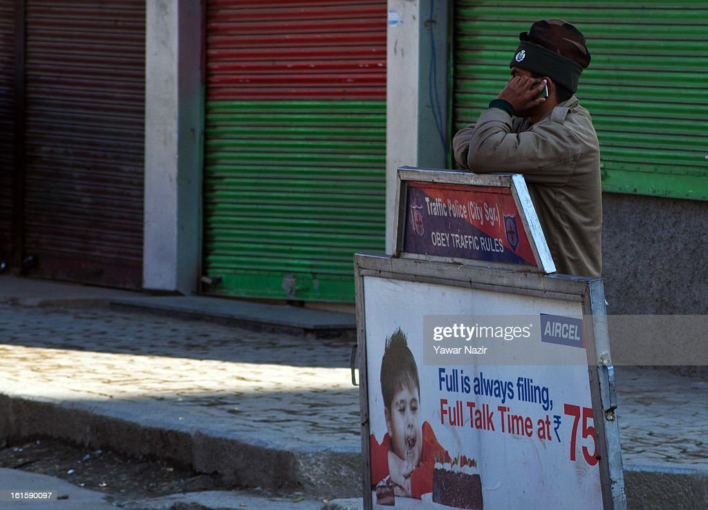 A police man speaks on cell phone as he guards city center during a curfew, imposed after the execution of alleged Indian parliament attacker Mohammad Afzal Guru on February 12, 2013 in Srinagar, the summer capital of Indian Administered Kashmir, India. Afzal Guru, from Sopore town in the north of Kashmir, was hung on February 09 for his role in the 2001 Indian parliament attack which left 14 dead. The hanging has further strained relations between India - who blamed the attack on 'Pakistan backed' militant group Jaish-e-Mohammed - and neighbouring Pakistan and has seen an military increase from both along the border.