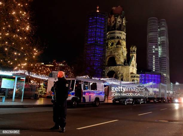 A police man stands at the site where a truck speeded into a christmas market in Berlin on December 19 2016 killing nine persons and injuring at...