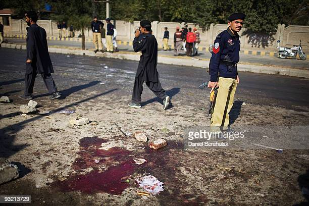 A police man stands guard at the the site of a suicide bomb blast on November 19 2009 in Peshawar Pakistan A suicide bomber detonated himself outside...