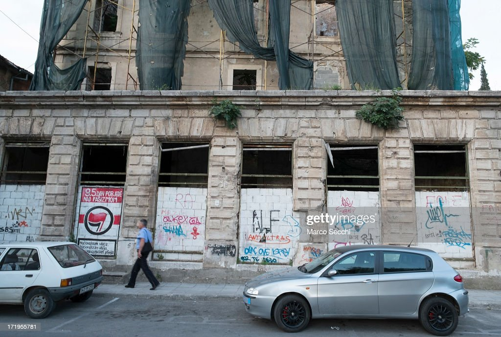 A Police man walks in front of a building damaged by bulletts from the 1993 war as the city of Mostar remembers the 1993 conflict on June 28, 2013 in Mostar, Bosnia and Herzegovina. The Siege of Mostar peaked in 1993 during the Croat-Bosniak conflict lasting eighteen months as fighting took place as Bosnia and Herzegovina declared independence from Yugoslavia. The city was divided in half between the two battling armies. Mostar, dating back over four hundred years, was mostly destroyed through the fighting. Although reconstruction has slowly commenced in the last decades, evidence of the war remains in bullet ravaged buildings still standing throughout the city.